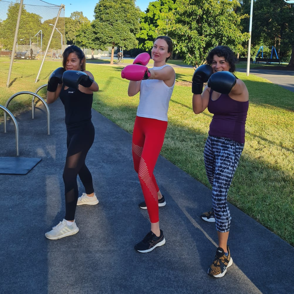 three girls posing with boxing gloves