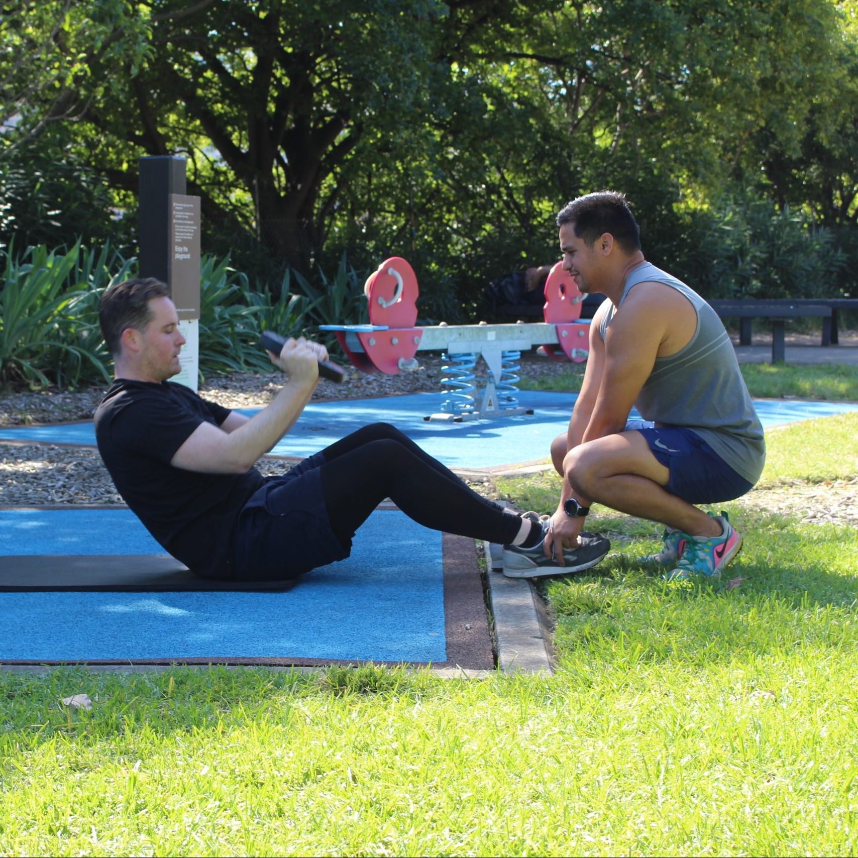 man doing pushups with a trx outdoors with a personal trainer
